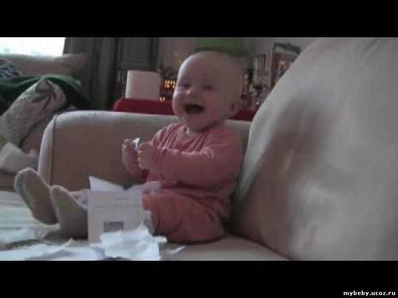 baby laughing at tearing paper